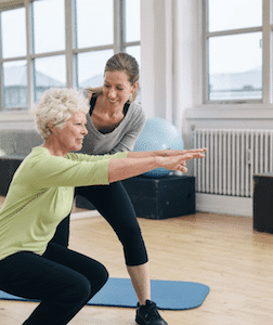 Hip pain professional teaching lady to squat