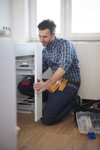 man assembles furniture maybe doing DIY with hip pain