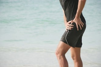 A male person at the beach, having severe hip pain, maybe due to hip osteoarthritis.