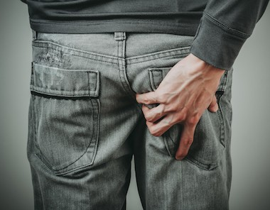 Man grabbing painful buttock with possible sciatica, piriformis syndrome or deep gluteal syndrome
