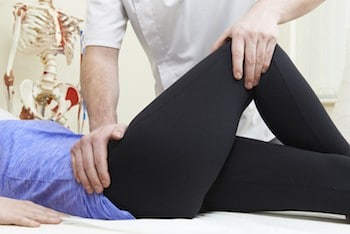 Male professional Treating Female Patient With Hip Pain