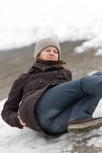 Woman slips and has a fall onto buttock on the ice
