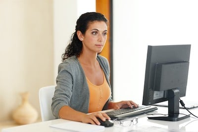 woman sitting painfree at desk who has had pain relief sitting