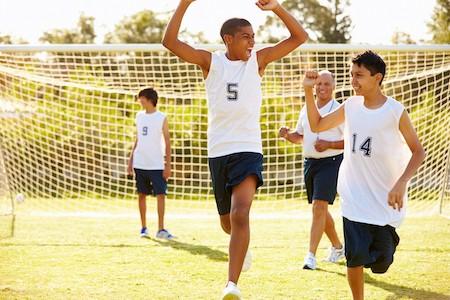 Player Scoring Goal In High School Soccer Match Celebrating
